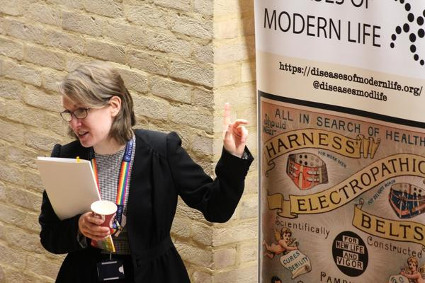Dr Catherine Charlwood stands in front of the Diseases of Modern Life Banner